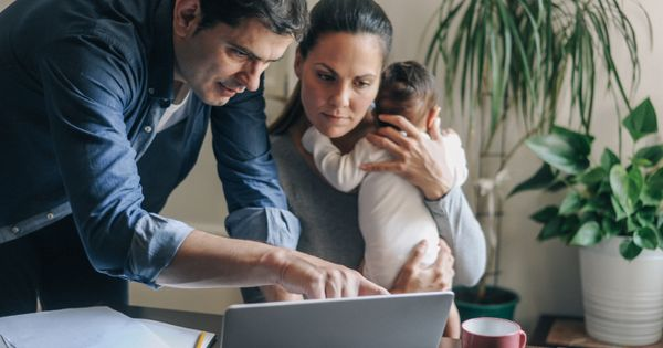 A man and woman look at a laptop while the woman holds a baby.