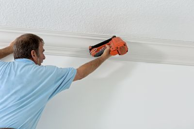 Tradesperson installing crown molding in a new home