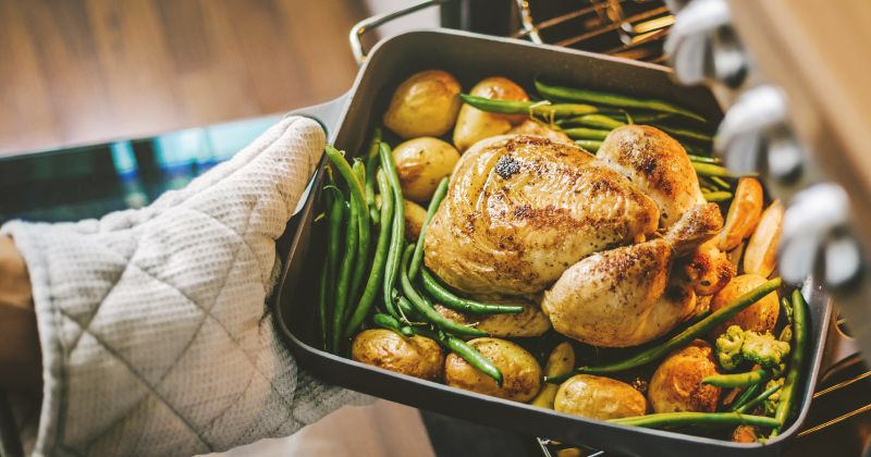 turkey and veggies in a roasting pan coming out of the oven