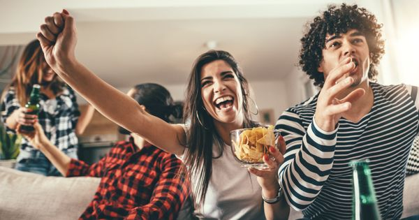 A group of people cheering while eating snacks in a home.