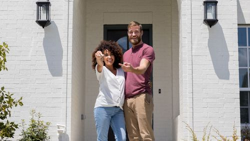 photo of couple in front of house with keys