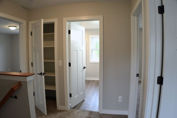View of the upstairs landing with doors to bedrooms, full bath and hall closet