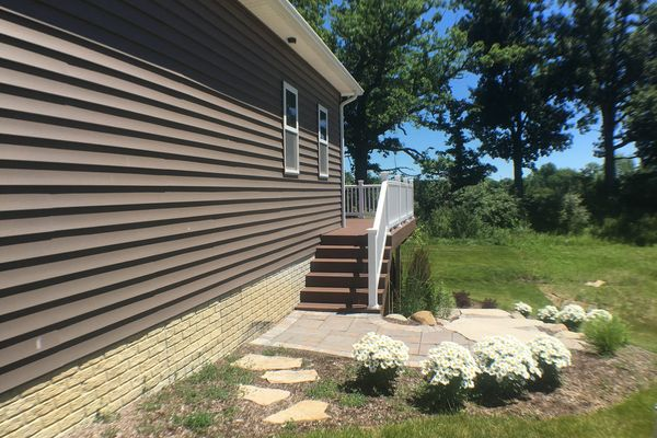 Composite decking stairs and stone path steps to backyard