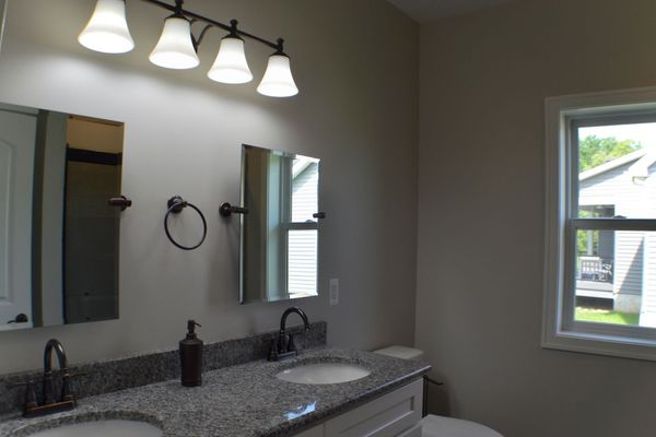 Master bath with dual sinks and granite countertops