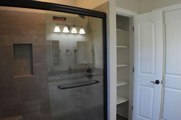 Tiled shower and linen closet