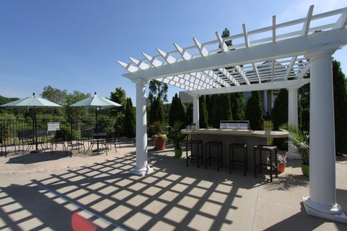 Grill by the pool at The Cove at Magnolia Lakes 55+ Living Cornerstone Homes