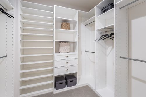 walk-in owner's closet white shelving closet organization