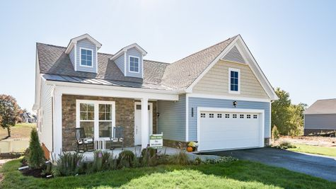 Exterior of craftsman style home with stone and front porch by Cornerstone Homes
