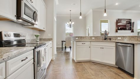 Kitchen with White Cabinets and Stainless Steel Appliances - River's Edge - DSLD Homes D'Iberville