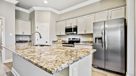 Kitchen with White Cabinets and Stainless Steel Appliances - Orleans Run - DSLD Homes Lake Charles