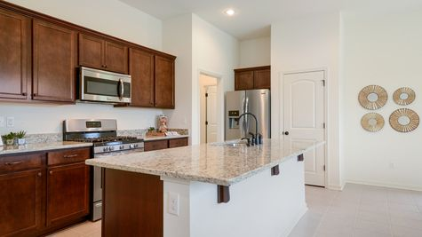 Kitchen- natural light- walk in pantry- granite countertops- open floorplan- dark wooden cabinets- tile floor- Model Home - DSLD Homes- Baton Rouge area - St. Gabriel- Louisiana- Meadow Oaks