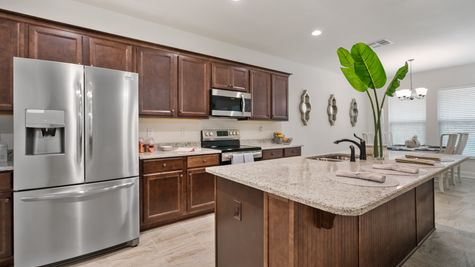 Kitchen with stainless steel appliances and brown cabinets - DSLD Homes - Foley - Cypress Gates