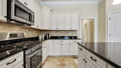 Kitchen with White Cabinets and Stainless Steel Appliances - Northern Oaks - DSLD Homes Pass Christian