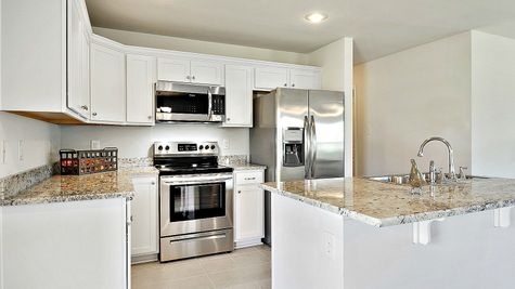 Kitchen with White Cabinets and Stainless Steel Appliances - Belvedere Place - DSLD Homes Gulfport