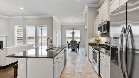 Kitchen-crown molding- stained cabinets- open floorplan- led lighting- tile- DSLD Homes- Baton Rouge area - Addis- Louisiana- Sugar Mill Plantation