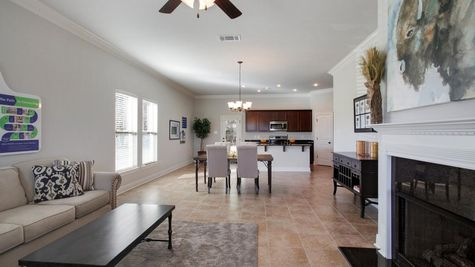 Agreeable Gray walls- Dark wooden kitchen cabinets- Fireplace mantel- open floorplan- Living room- Oak Grove Model Home-  Iowa Louisiana- Lake Charles area-DSLD Homes