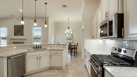 Kitchen with White Cabinets and Stainless Steel Appliances - Spring Lakes- DSLD Homes Covington