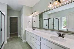 Owner's bath - framed mirror, tiled floor, and quartz tops