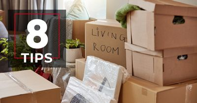 """Moving boxes being packed with """"8 TIPS"""" in the Homes by Taber design in the top left corner."""