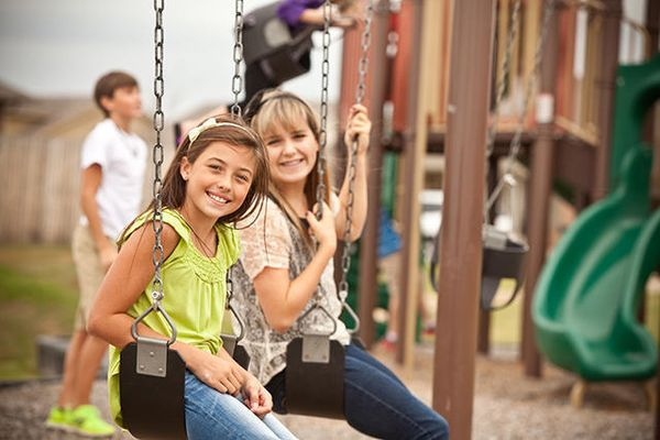 Children playing in a park at Trail Woods, a community of Norman OK new homes from Ideal Homes