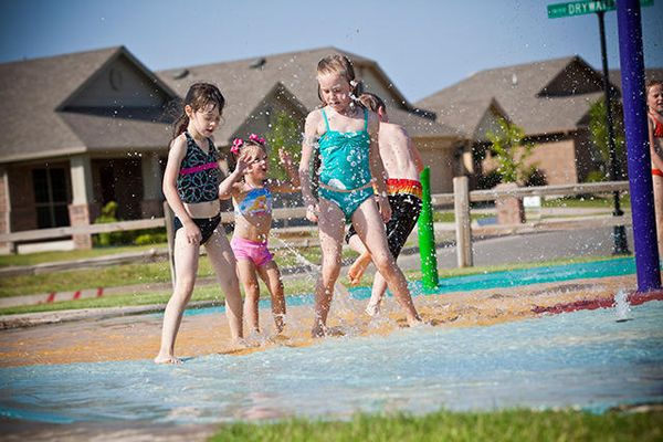 Children playing in a Featherstone Community pool around our new homes in Moore OK from Ideal Homes