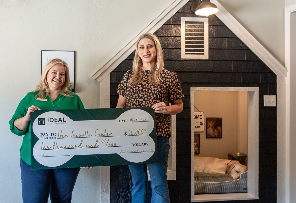 Ideal Homes & Neighborhoods giving donation check to Saville Center in Stillwater