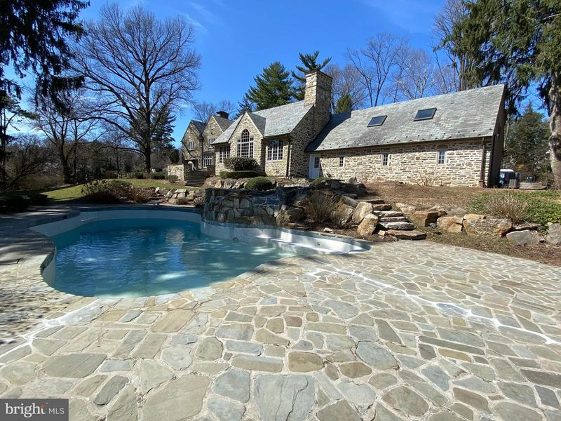 Stone estate home with in ground pool and stone patio