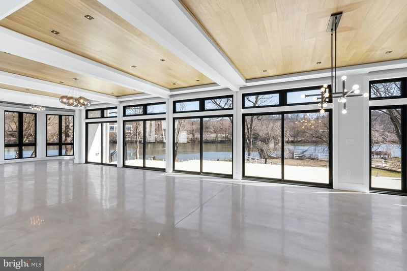 View of Schuylkill River from room with polished concrete floor, black trim windows, natural wood and white trim ceiling