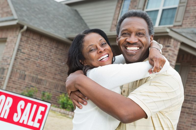 Homeowners embracing in front of the home they're selling
