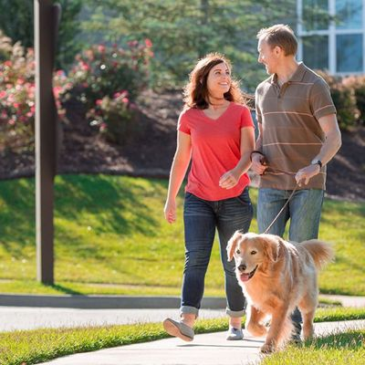 Couple walking their pet in a new home community