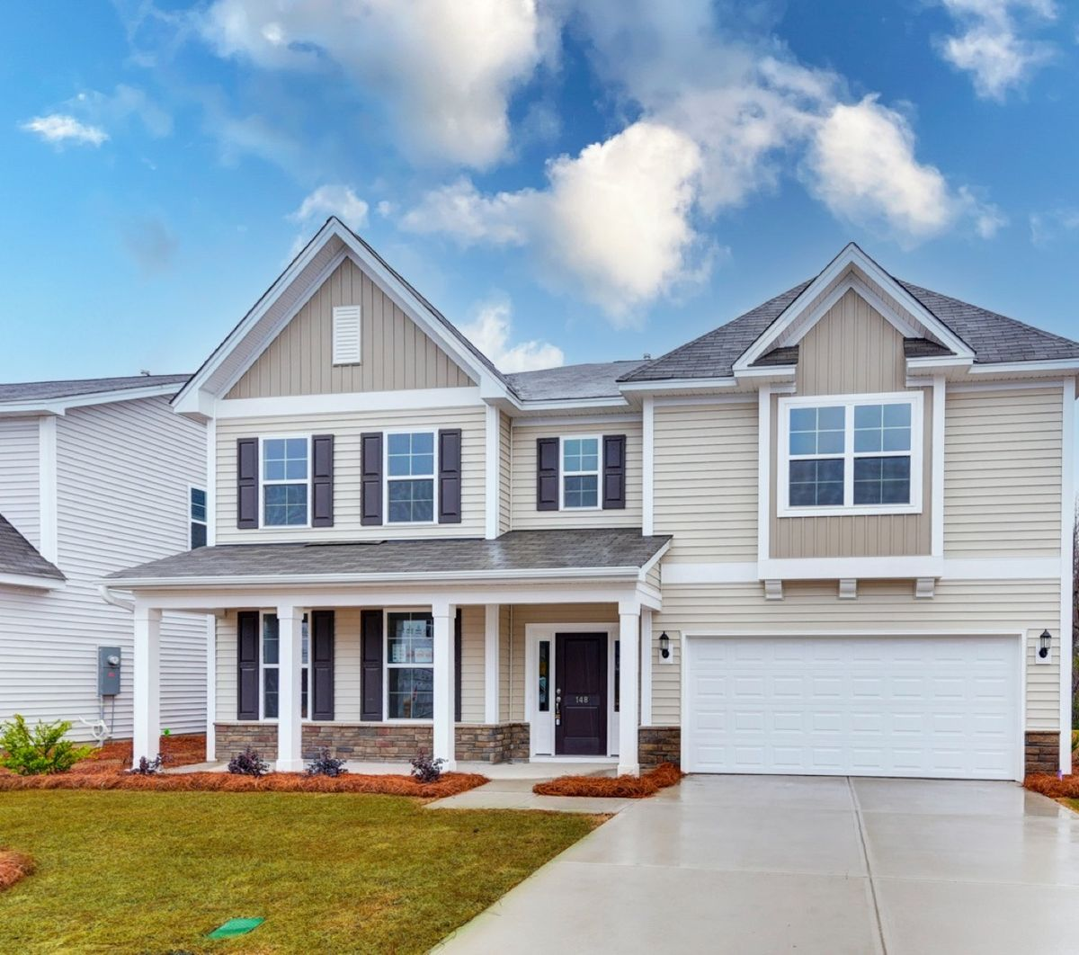 Beige two-story home with front porch