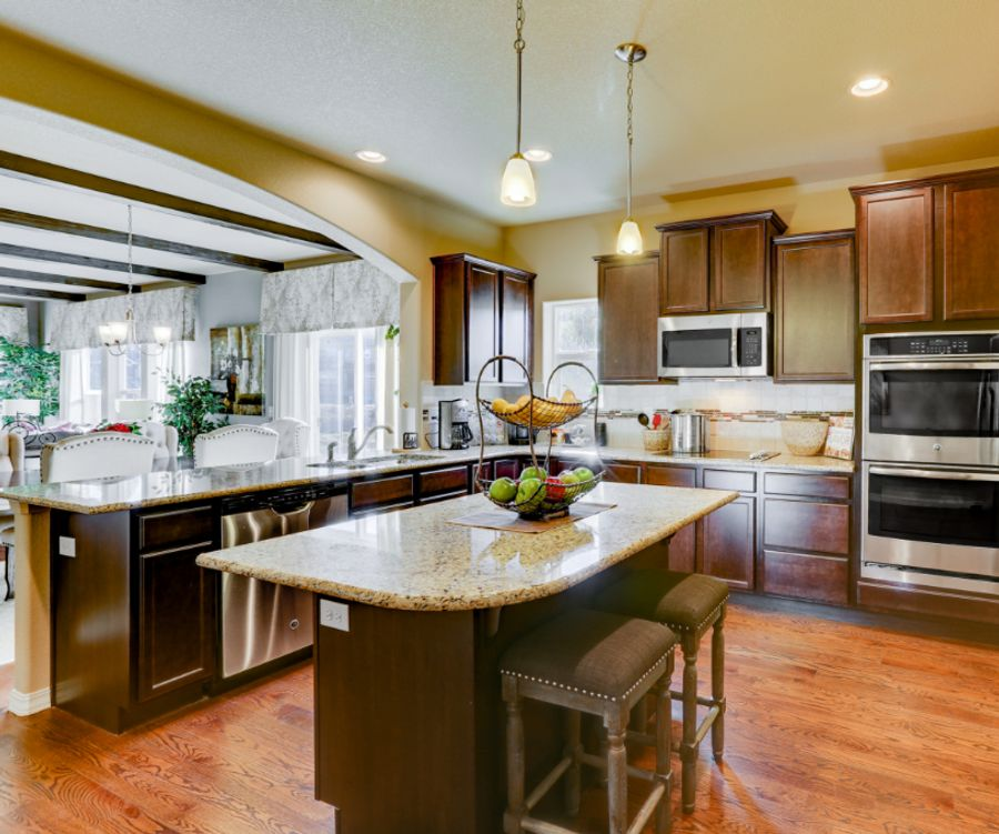 modern kitchen featuring granite countertops, dark wood cabinets, and stainless steel appliances