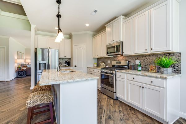 The Jasmine model home kitchen with white cabinets, island with pendant lights, granite counters, wood floors.
