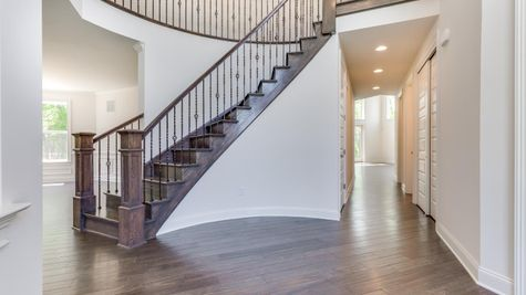 Curved stair case in front hall of The Stoneleigh luxury home model, with dark hardwood floors & stairs, decorative handrail.