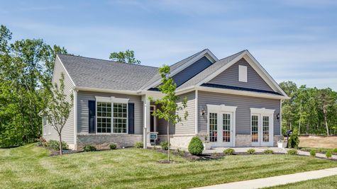 Exterior of the Zinnia sales office & model new home in South New Jersey with gray siding and colonial accents.