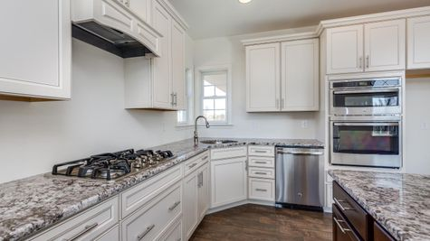 Avignon Kitchen with white cabinets granite counters, stove, double oven, wood floors.