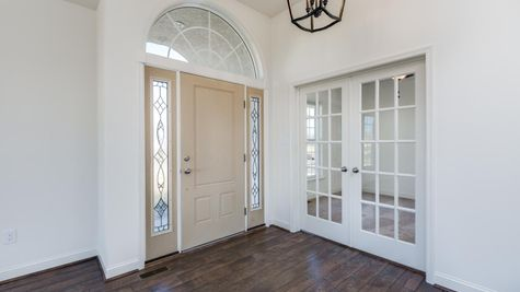 Interior of Avignon model new home, front foyer, front door & windows, plus glass doors to home office visible