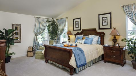 Baldwin model home master bedroom with high ceiling and sample furniture.