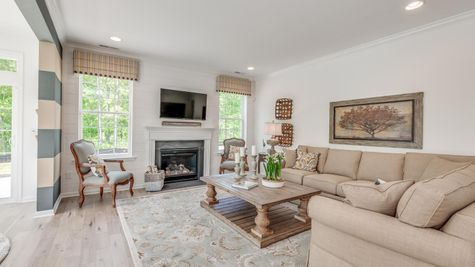 Family room of Zinnia with fireplace on back wall, large windows on either side, sample house furniture in Zinnia model home.