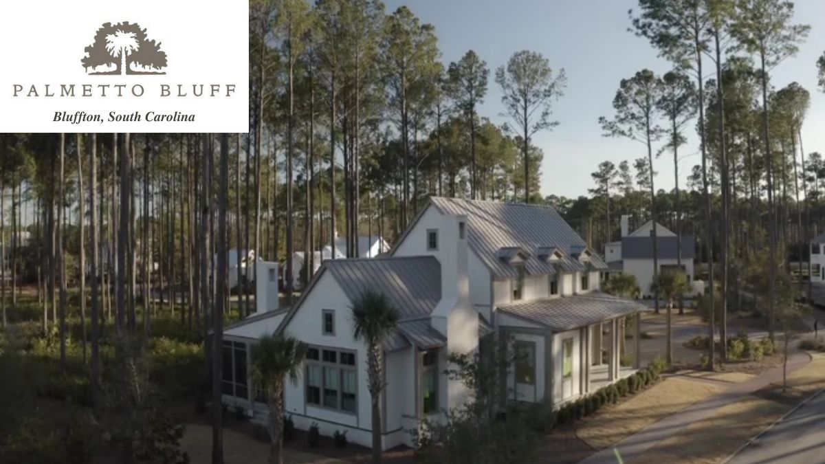 New luxurious home in Bluffton South Carolina, white with gray roof, front porch, surrounded by pine trees.