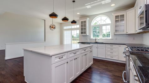 Baldwin kitchen with large island, white cabinets, decorated arched transom window over sink, slider door to outside.