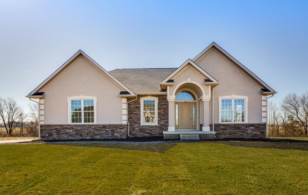 Exterior of one story ranch style Avignon model new home in NJ with stucco and stone plus portico over front door.