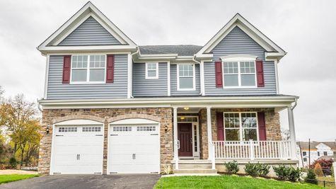 Oakton Grand new home in NJ with gray siding & stone facade, maroon shutters, double peak roofline, veranda, 2 garages.
