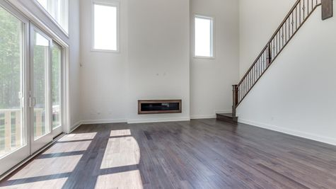 Stoneleigh family room with small fireplace, large windows, back staircase to the right, slider door to outside on left.