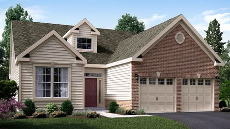 The Marigold Manor one story active adult home in NJ with brick surrounding 2 garage doors, tan siding and colonial trim.