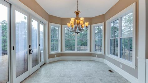 The Stoneleigh optional morning Room, with many windows and large central chandelier, sliding doors to outside.