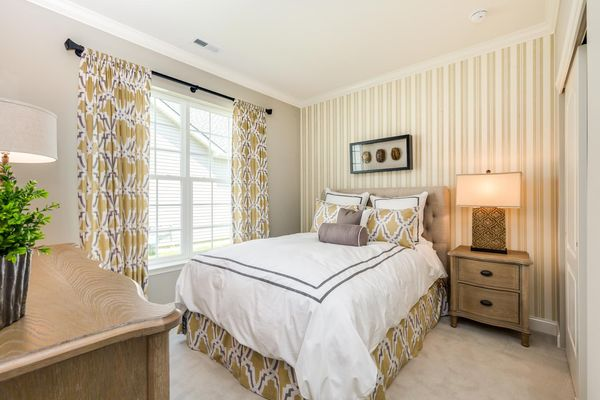 Jasmine model home second bedroom with large double window, decorated with sample furniture.