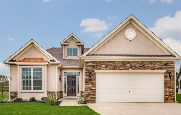 Exterior of the one story, ranch style Magnolia model new home in South NJ with stucco and stone, plus 2 car garage.