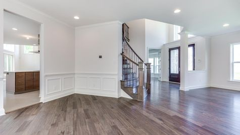View of the Stoneleigh front entry hall from the dining room, white halls, columns, hardwood floors, two story Entry.