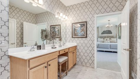 Master bedroom bathroom with double sink vanity in Zinnia model home decorated with wallpaper.